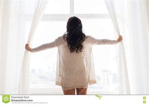 curtain people close up of happy woman opening window curtains stock