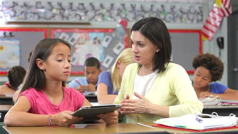 Elementary School Student And Teacher Look At Computer Student Working At Desk