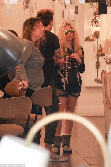 pop star with red curly hair avril lavigne flashes bra as she and ryan cabrera shop for