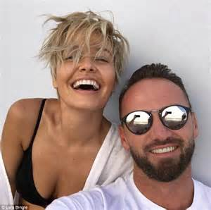 Lara Bingle smiles with Travis Balcke as she showcases her