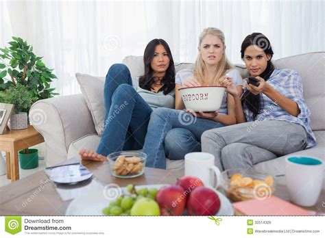 couch sharing friends sharing bowl of popcorn and watching television