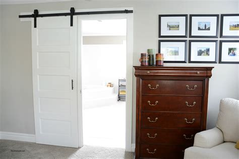 White Stained Wood Sliding Barn Door Hanging On Black Rod Hanging Sliding Barn Doors