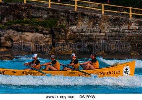 boat club manly men and a surf life saving rowing boat on beach at a surf