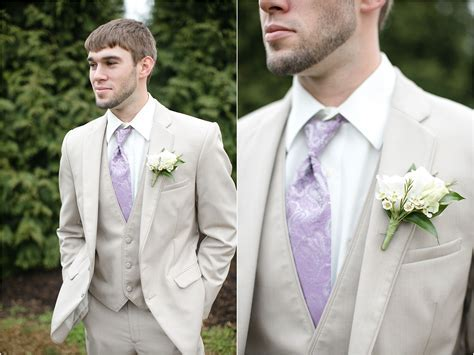 This groom's cream suit, purple tie, and boutonniere are