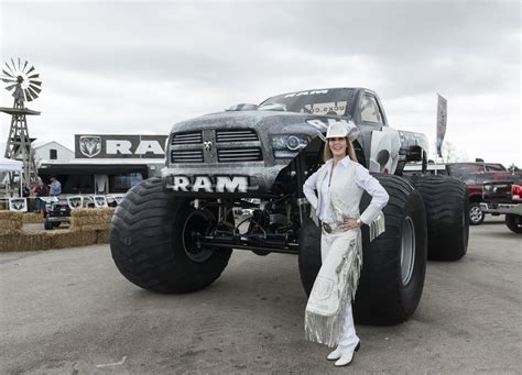 outdoor monster truck woman in white clothes standing next to grey ram monster