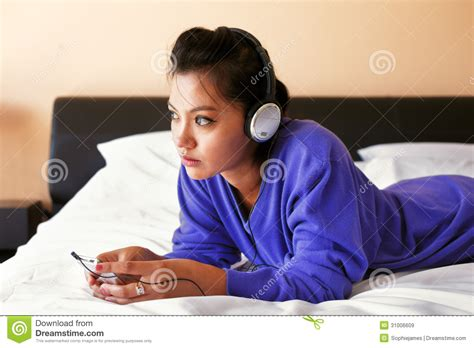 free music beds young woman in headphones listening to the music in bed royalty free stock images