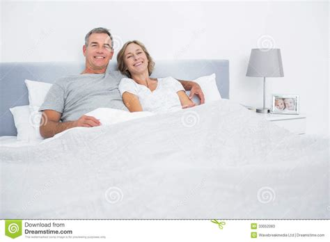 cuddle in bed cheerful couple cuddling in bed looking at camera stock