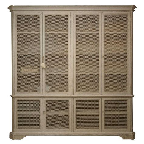 large cabinet in distressed grey paint with wire mesh doors