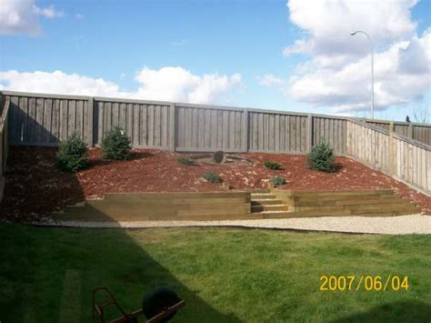 how to make a sloped backyard flat this steep slope is retained with an anchored wall using