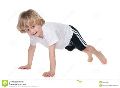 small tiny cute boy performs gymnastic exercises stock photo image