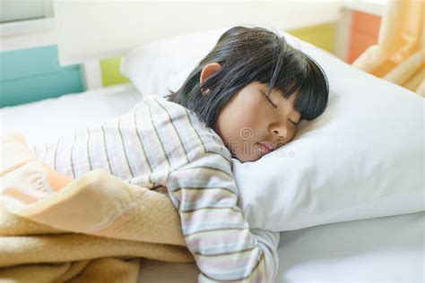 sleeping in asia asian girl sleeping on bed covered with blanket stock