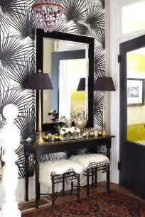 Entryway with patterned walls wooden table wood framed mirror and