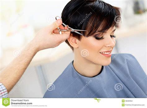 hairdresser cutting woman s hair in beauty salon haircut