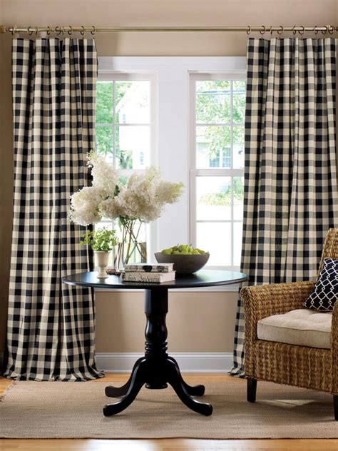 Simple living room with black buffalo check curtain panels and round black wooden end table