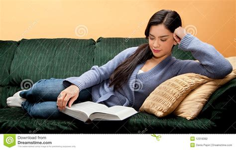 laying couch young woman lying down on sofa and reading book stock