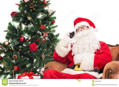 images of christmas tree and santa claus santa claus with smartphone and christmas tree stock photo