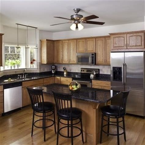 Oak Cabinets with stainless and white appliances and black