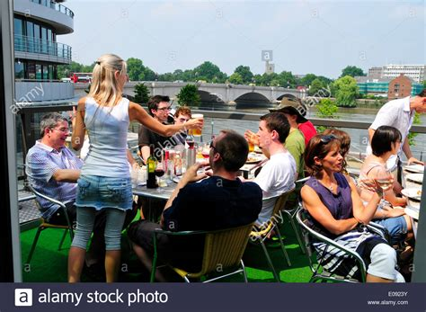the boat house putney drinkers on the balcony of the boathouse pub putney london england stock photo