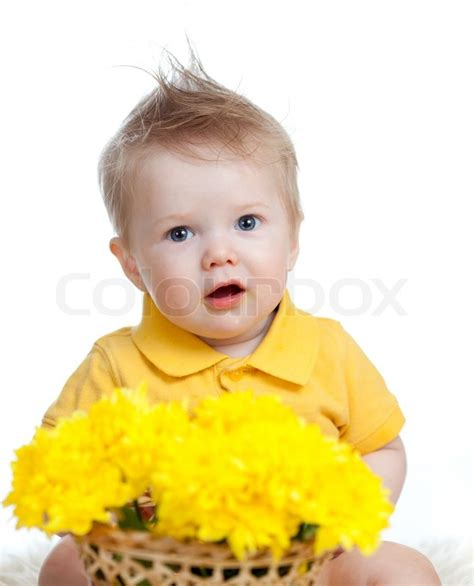 cute child cute baby boy holding basket with yellow flowers stock