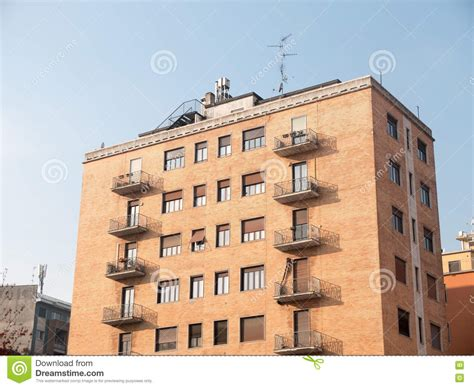 brick apartment building with small balconies stock photo
