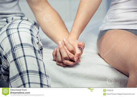 images of love hands together young couple holding hands sitting over a bed stock photo