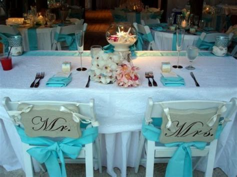 white tiffany chairs for outdoor wedding with aqua napkins