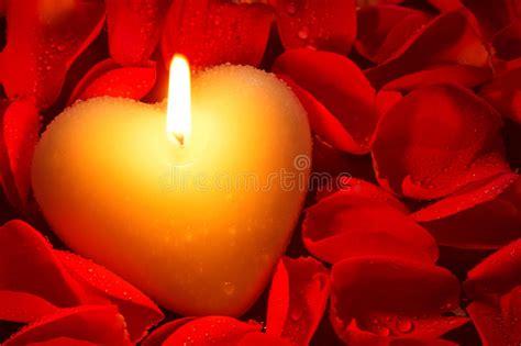 candele e petali di rosa candela di forma cuore e petali rosa immagine stock