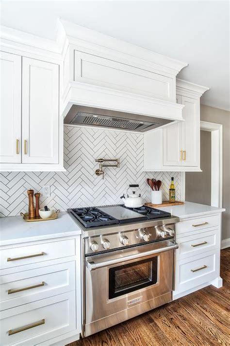 red brick herringbone kitchen cooktop backsplash