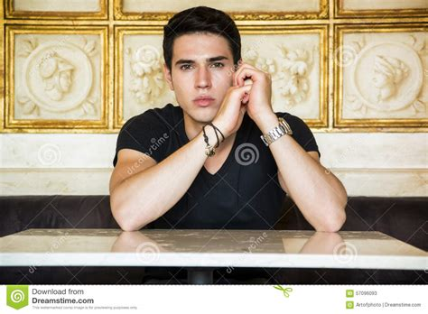 comfortably seated relaxed young man sitting comfortably at table stock photo