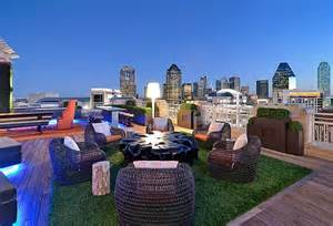 Modern rooftop design with grass rug and confy rattan chairs