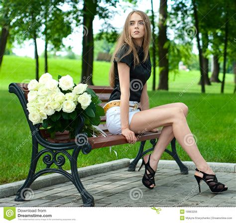 girl bench young girl sitting on a bench in a large bouquet o stock