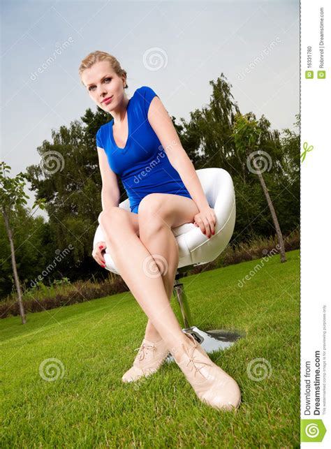outdoor sitting blonde girl sitting outdoor on a swivel chair stock photo