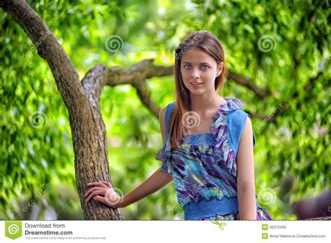 beautiful woman by the tree looking up stock photo image portrait of a beautiful young teenager girl stock photo