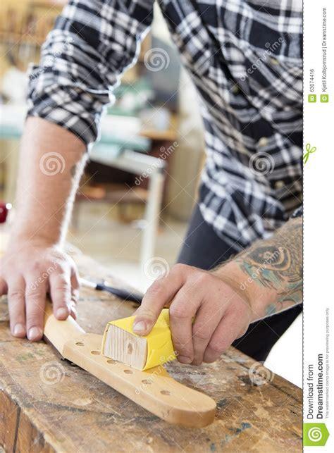 working man tattoo carpenter sanding a guitar neck in wood at workshop stock