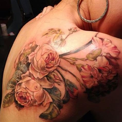 the pink feminine roses in this feminine tattoo have an