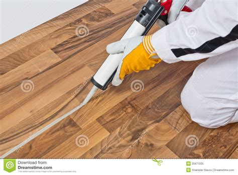 Worker Applies Silicone Sealant On Wooden Floor Royalty