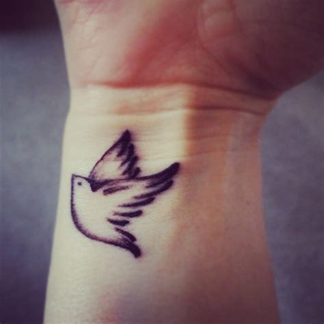 small dove wrist tattoos black ink flying bird on wrist
