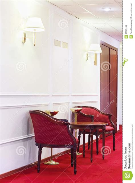 dos butacas rojas  la tabla de madera redonda en la alfombra roja foto de archivo libre de