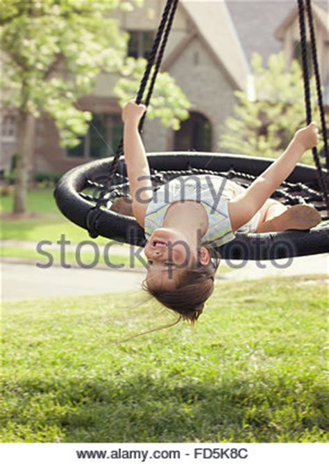 upside down swing a girl hanging upside down with eyes closed stock photo