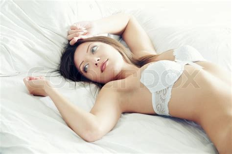 pretty with white camisole laying on the bed at early