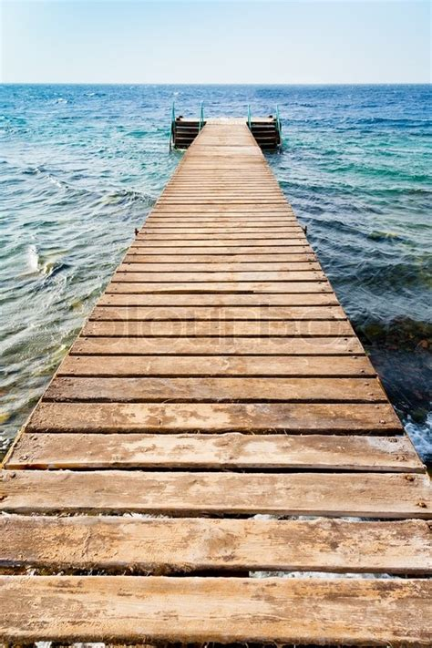 wooden pier on coast of coral beach stock photo colourbox