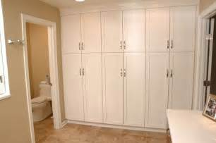 Wall of streamlined tall cabinets provides storage in this bathroom