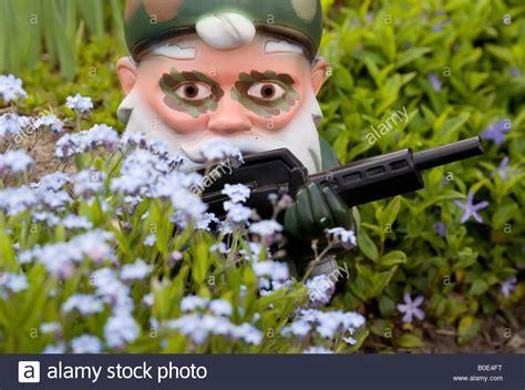 garden gnomes with guns garden gnome in camouflage with machine gun behind flowers
