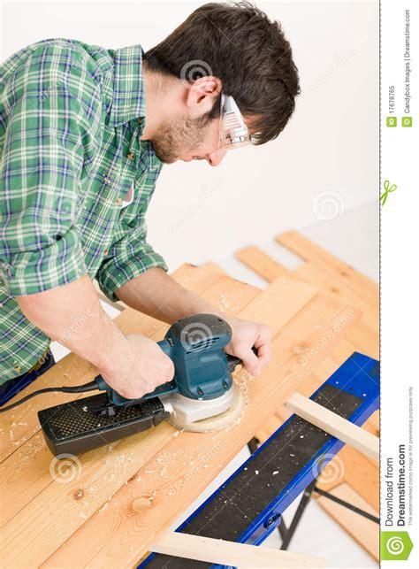 home improvement handyman sanding wooden floor royalty