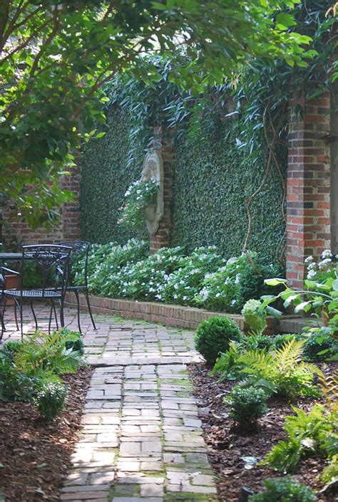 Brick Wall Garden Courtyard With Plant Covered Walls And Wall