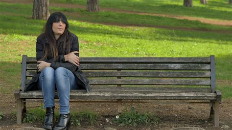 people sitting on a park bench chilly and anxious woman sitting alone on a bench of a