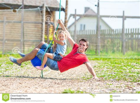 is swinging fun happy family having fun on a swing outdoors stock photo
