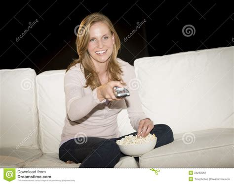 having on the sofa woman watching tv while having popcorn on sofa stock