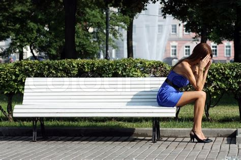 sitting in a park bench young woman sitting on a park bench stock photo colourbox