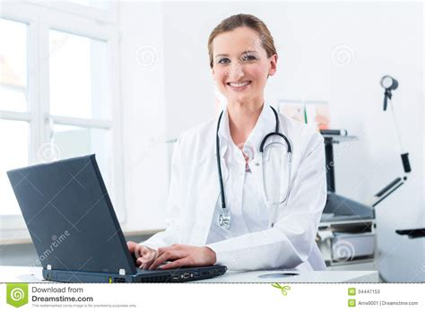 The Desk Doctor by Doctor Writing On Pc In Clinic Stock Photos